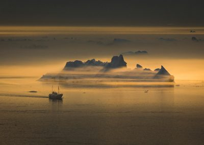 A fishing vessel passing an iceberg shrouded in fog near Ilulissat ice fjord in Greenland