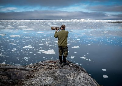 A photographer at work by the Sermilik Icefjord in East Greenland