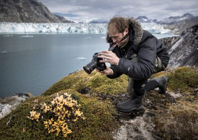 A photographer shooting flowers and plants by the Knud Rasmussen Glacier in East Greenland
