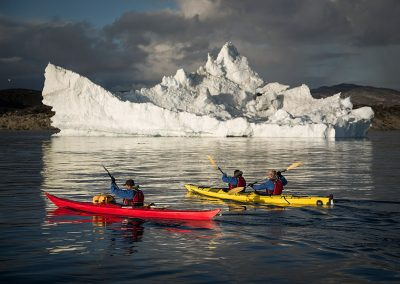Kayakers from PGI Greenland paddling home to Oqaatsut near an iceberg in the Disko Bay in Greenland